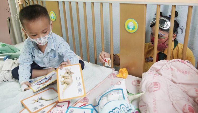 隔著病床的柵欄,小丑醫生朱怡文遞出了象徵友誼的名片給正在排列動物卡片,對她愛理不理的病童。(季志翔攝)