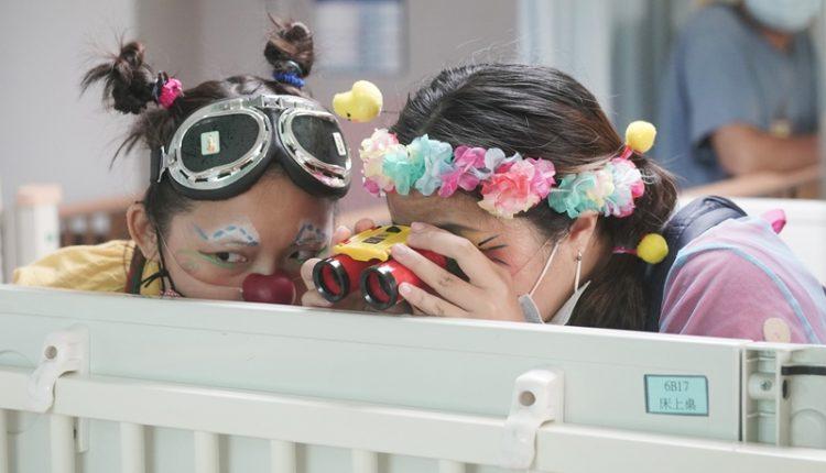 小丑醫生蔡孟純(右)與朱怡文(左)隔著病床,有模有樣的拿出望遠鏡觀察,試圖用最輕鬆自然的方式打動小朋友的心。(季志翔攝)